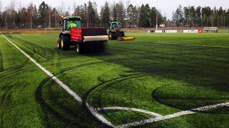 Granulat sprids ut på konstgräsplan. Foto: Janne Rindstig/Sveriges Radio