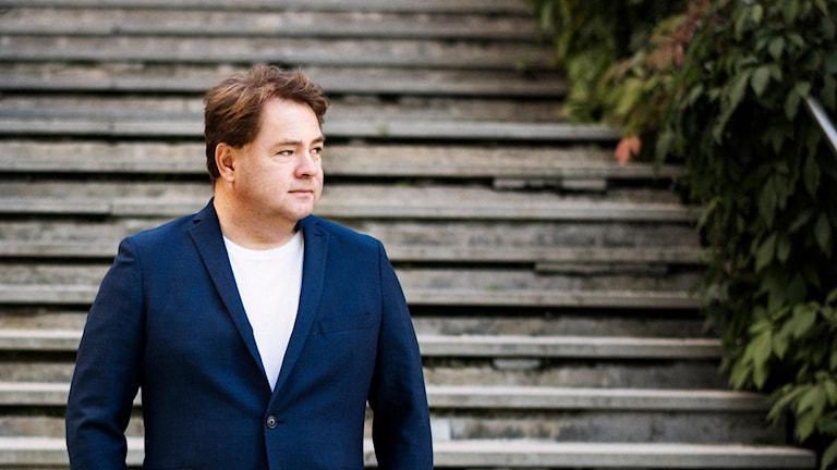 En man i blå kavaj framför en stentrappa.