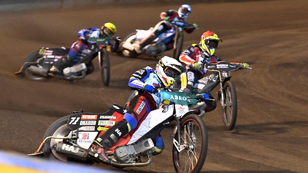 Fyra speedwayförare kör motorcyklar.