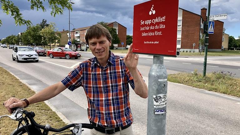 EN man står med en cykel vid en skylt där det står: 'Se upp cyklist, just här ska du låta bilen köra först. Tack för att du cyklar!''
