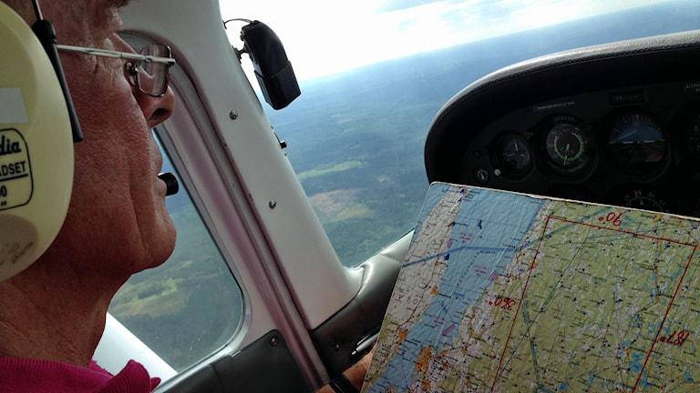 En pilot sitter i cockpit i sitt plan med en karta framför sig samtidigt som han blickar ut ut över skogslandskapet under planet.