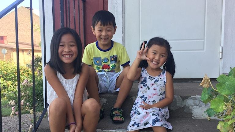 Tre barn sitter på trappa