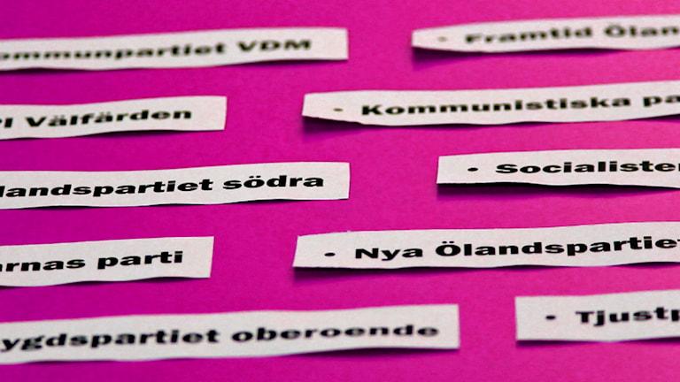 Små lappar med partinamn på rosa  bakgrund.