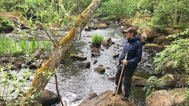 En man i mörkblå jacka och brun keps står vid ett grunt vattendrag.