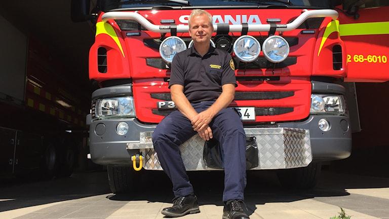 Räddningschef Ingemar Idh sitter i solen på fronten på en brandbil.