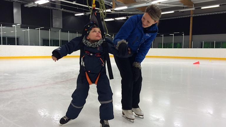Elias åker skridsko med sele och får hjälp av Julia. Foto: Peter Bressler/Sveriges Radio
