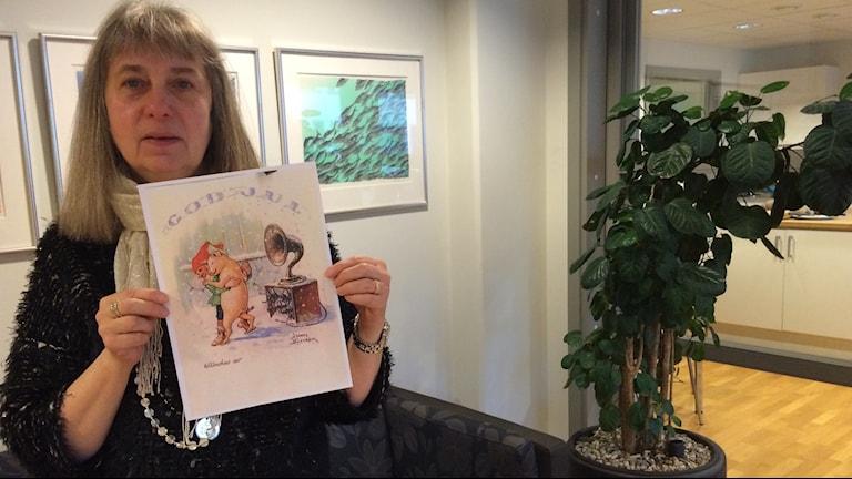 Barbro Johnsson, ansvarig tjänsteman för Jenny Nyströmstiftelsen, visar upp en kopia på den senaste Jenny Nyströmtavlan de köpt in. Foto: Marcus Léonarde/Sveriges Radio.