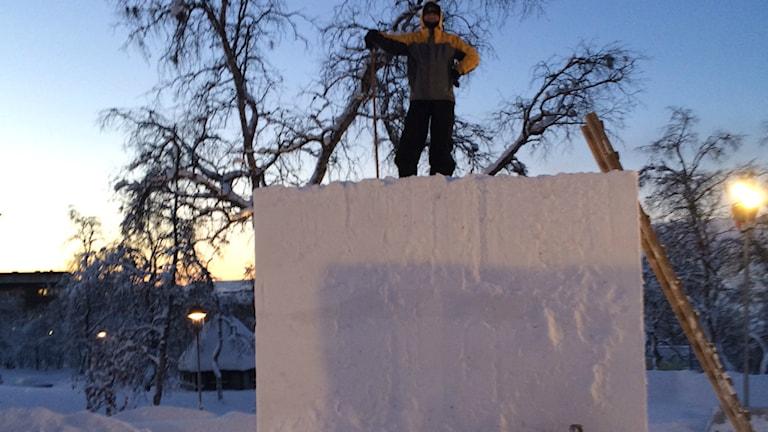 Konstnären Lars Fager står på en kub av 27 kubikmeter snö som han ska göra skulptur av. Foto: Edwin Böck..