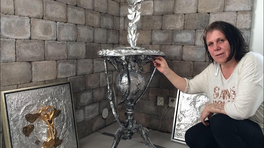Vad sägs om ett fontänbord i insvept i aluminium? Kicki Olsson visar upp sin skapelse i sitt galleri i Halltorp söder om Kalmar. Foto Peter Bressler Sveriges Radio AB