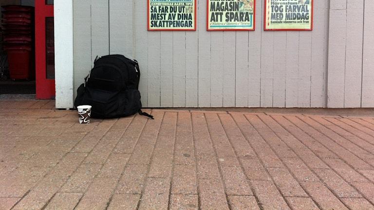 En tiggares plats mugg och väska utanför matbutik. Foto Erika Norberg Sveriges Radio