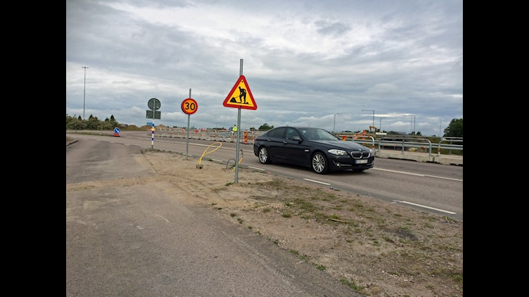 Bil kör förbi vägarbete