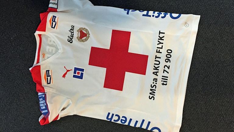 Vit tröja med Röda korsets logga på, som Kalmar FF spelar i för att samla in pengar till flyktingkrisen.