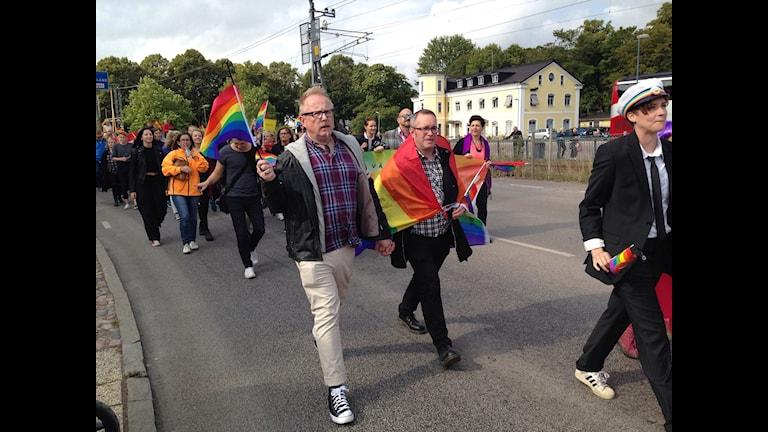 Två män håller varandra i handen iklädda prideflaggor.