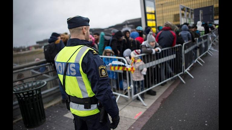 En polis övervakar kön av ankommande flyktingar i Malmö. Foto: Johan Nilsson / TT.
