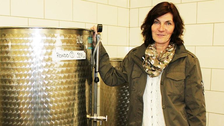 Vinodlaren Eva Gustafsson i Beteby står vid ståltankarna där alkoholjäsningsprocessen är i full gång. Foto: Alexander Jungå/Sveriges Radio