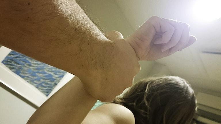 Man håller i kvinnas arm. Arrangerad bild. Foto: Nick Näslund/Sveriges Radio