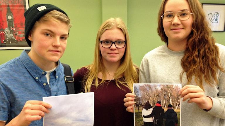 Elias Lindholm, Vilma Rydstedt och Moa Håkansson håller upp bilder från besöket.