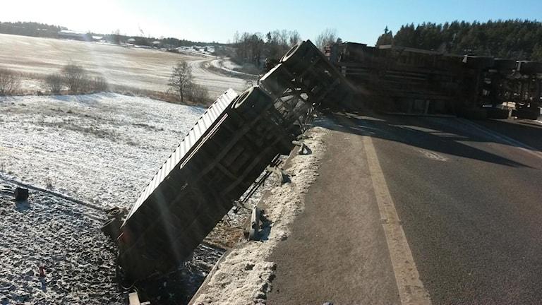 Lastbilstrailer hänger över brokant.