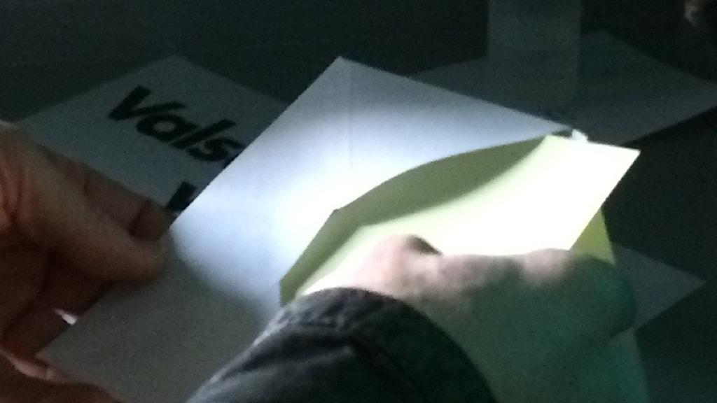 En hand lägger in en valsedel i ett kuvert.