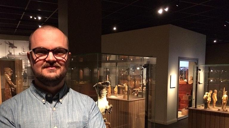 Ola Lundin, antikvarie på Döderhultarmuseet framför flera av montrarna i museet.