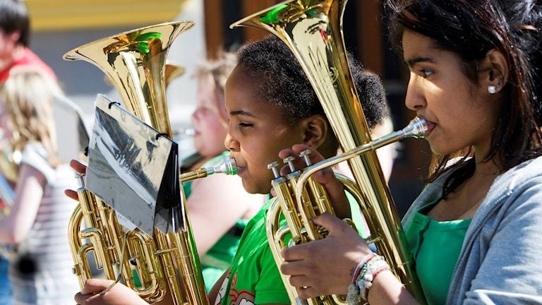Barn med blåsinstrument.
