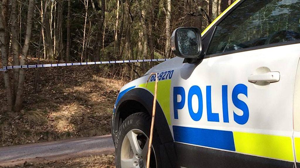Polisbil och avspärrning vid ett skogsparti.