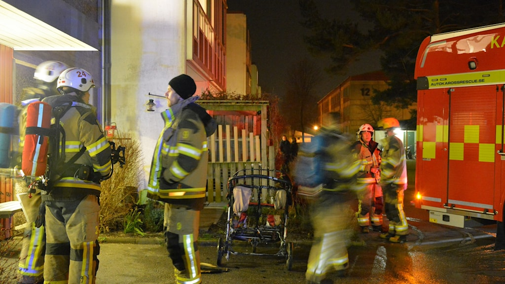 Brandmän utanför lägenhetshus och utbränd barnvagn.
