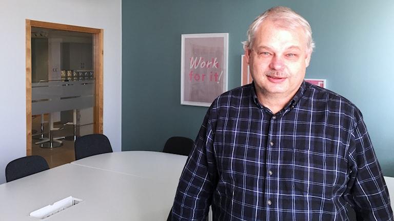 Roger Holmberg står vid ett vitt bord framför en tavla.