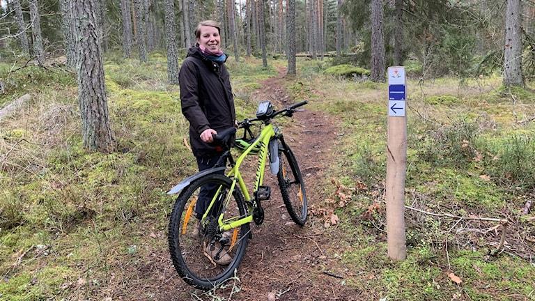 Ylva Eriksson, natur- och friluftsutvecklare i Nybro kommun, med mountainbike i skogen.