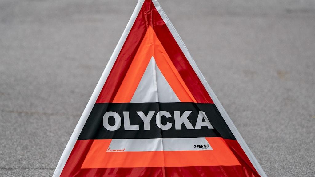 """Varningsskylt med texten """"olycka"""" på en asfaltsväg."""