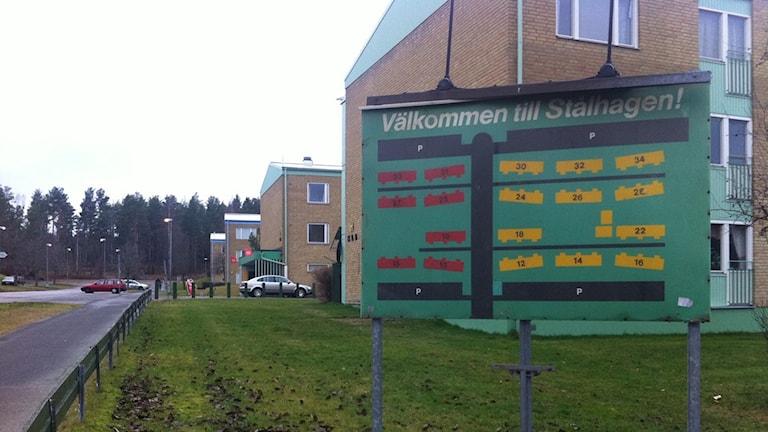 Skylt i förgrunden över området Stålhagen i Hultsfred, i bakgrunden gula tegelhus i tre våningar.