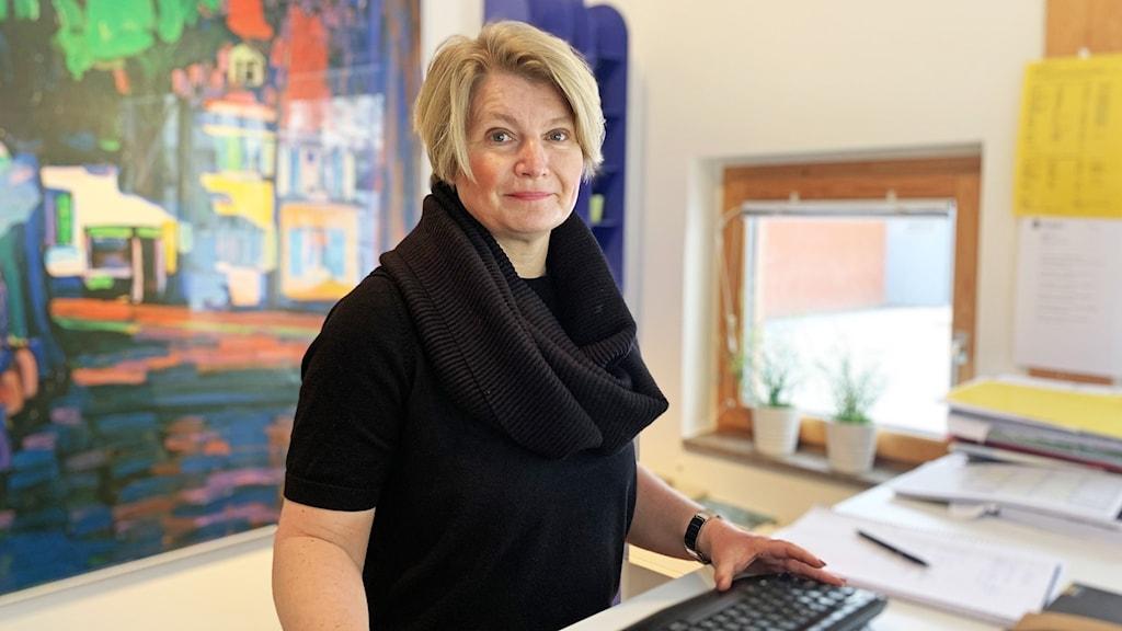 En person står vid ett skrivbord och har ett tangentbord framför sig.