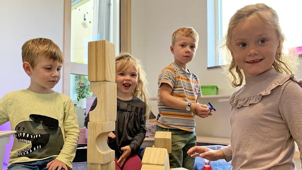 Fyra barn leker med träklossar.