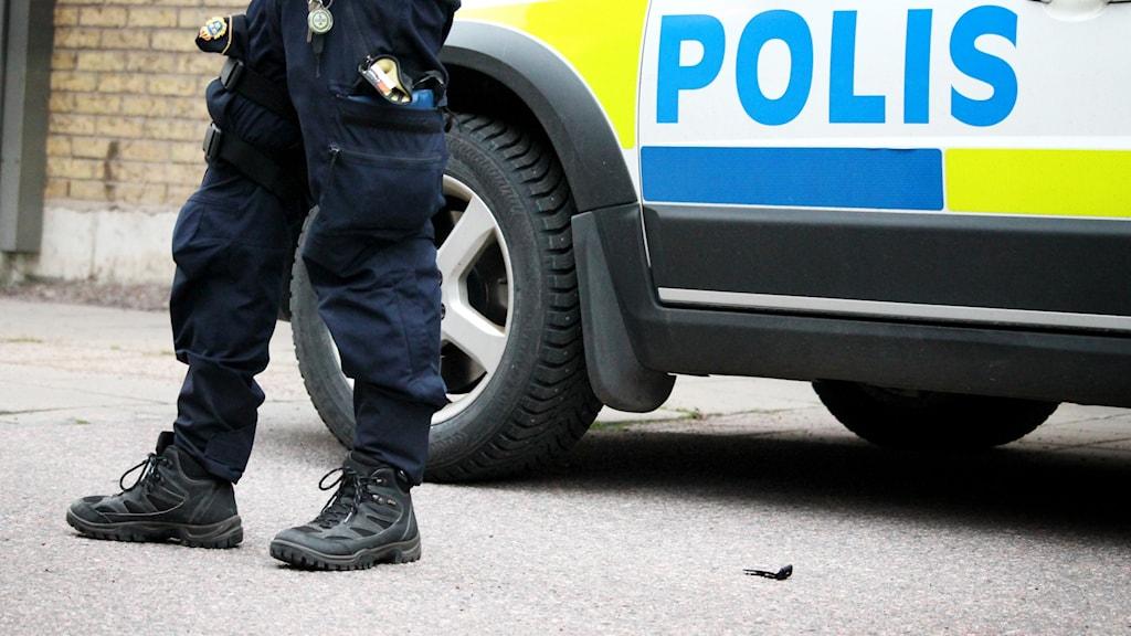 Polisman och polisbil.