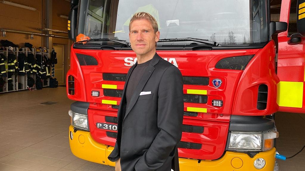 Man står framför en brandbil.
