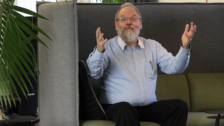 En man sitter i en grön soffa och slår ut med händerna.