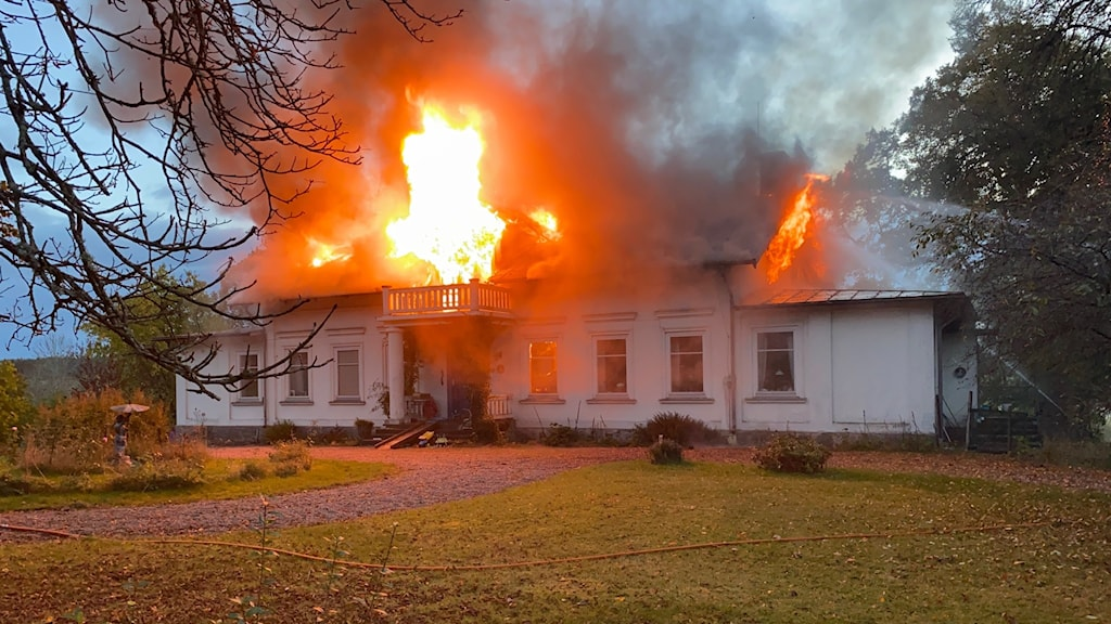 En villa brinner med lågor som slår ut från taket.