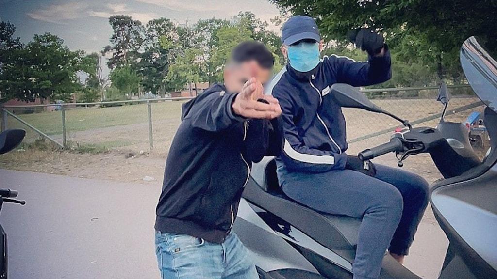 En kille pekar mot kameran med fingrarna som en pistol och en kille sitter på en moped bredvid.