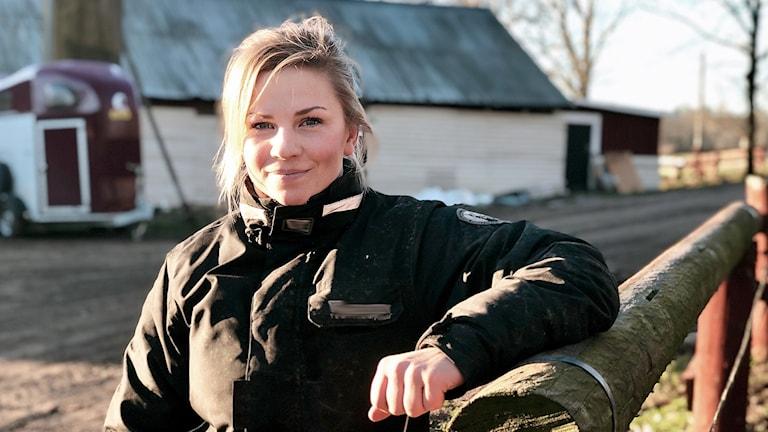 Emma Johansson står på en gård. Blont uppsatt hår. Rosiga kinder. Ler in i kameran.