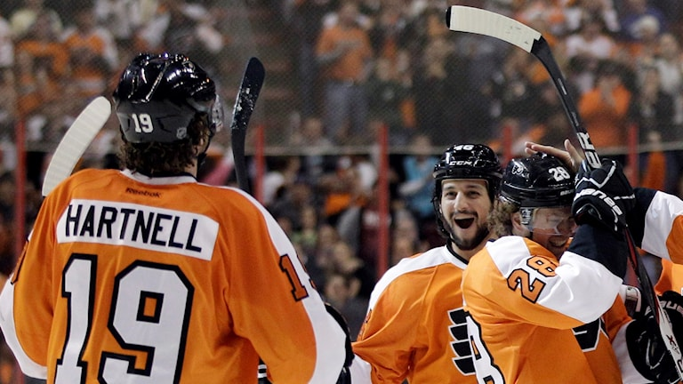 Tre hockeyspelare jublar.