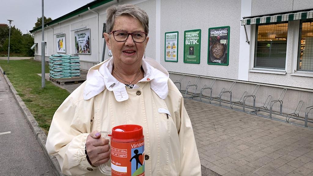 En kvinna står utanför en affär med en insamlingsbössa i handen.