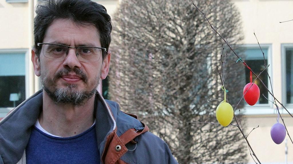 Nikos Galanis med svart hår, svart skägg och glasögon.