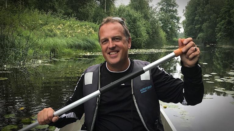 En man i kanot på ett vattendrag.