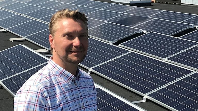 Mikael Wall står vid solcellspaneler.