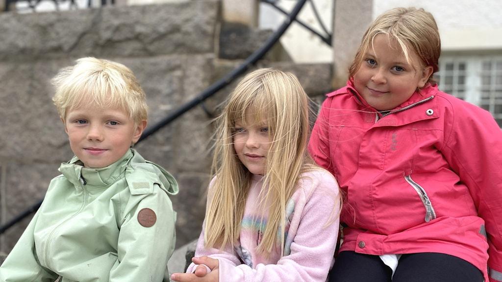Tre yngre barn som sitter i en trappa.