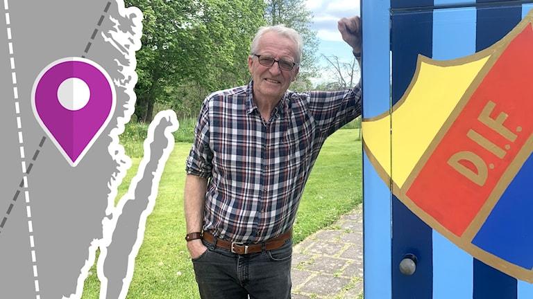 En man som står vid en gammal telefonkiosk som är målad i fotbollslaget Djurgårdens färger.