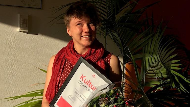 Pauline Fransson, konstnär, med blommor och diplom.