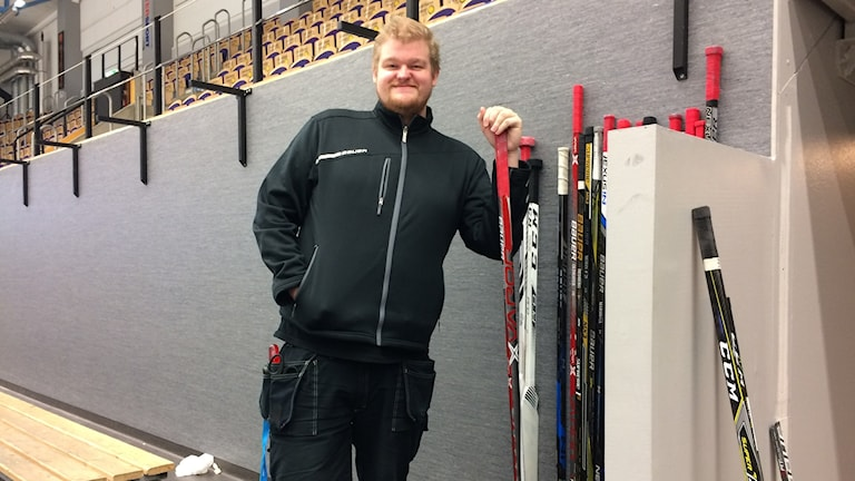 Benny Boqvist ståendes i ishallen med ishockeyklubba i handen och ytterligare ett tiotal uppställda mot den gråa väggen bakom honom.