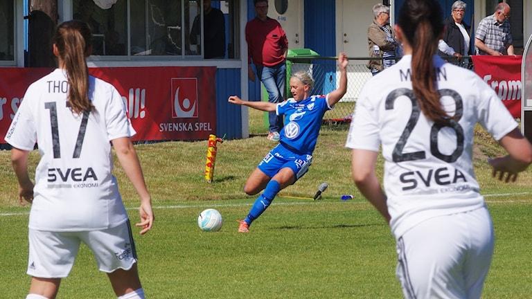 Tre fotbollsspelare. En i blått och två i vitt.