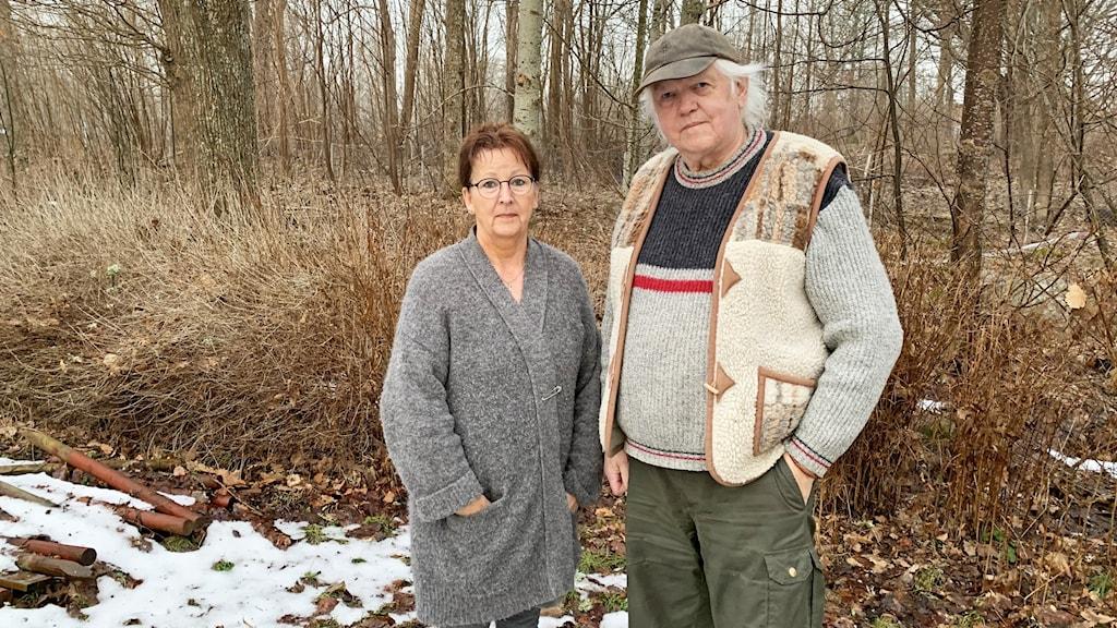 Två personer står utomhus framför en skog. Snö på marken.